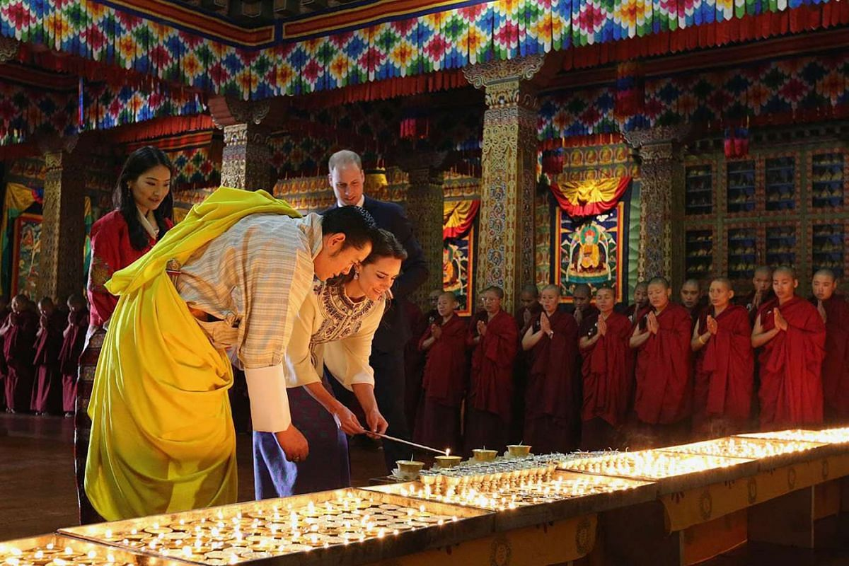 Bhutan's King Jigme Khesar Namgyel Wangchuck helps Catherine, Duchess of Cambridge, light candles as the Duke of Cambridge Prince William and Queen Jetsun Pema look on at the Grand Kuenrey of the Dzong, in Thimphu.