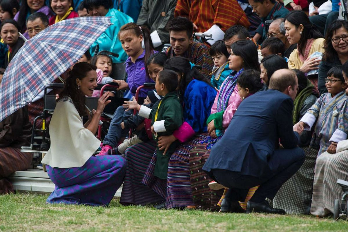 Britain's Prince William and his wife Catherine greet local children and their parents during an event at the Changlingmethang National Archery ground, on April 14, 2016.
