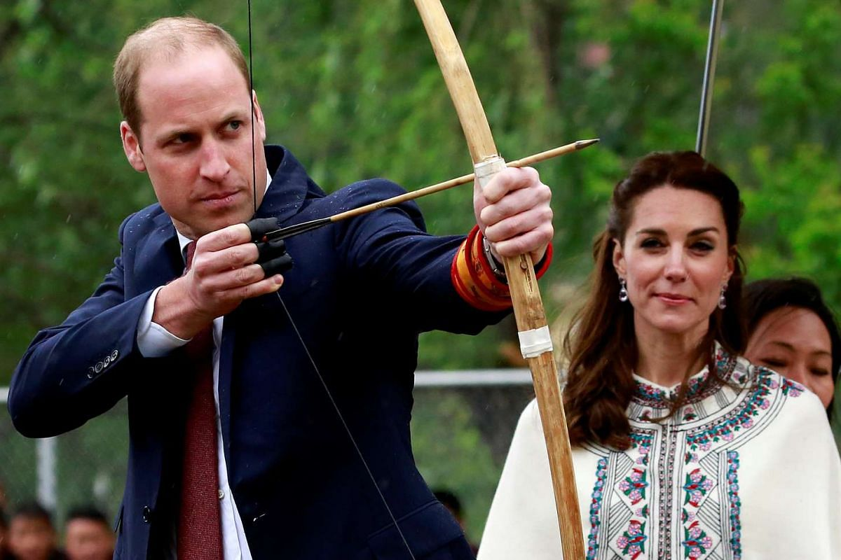 Britain's Prince William, Duke of Cambridge, prepares to shoot an arrow as Catherine, Duchess of Cambridge, looks on at Changlimithang Archery Ground, on April 14, 2016.