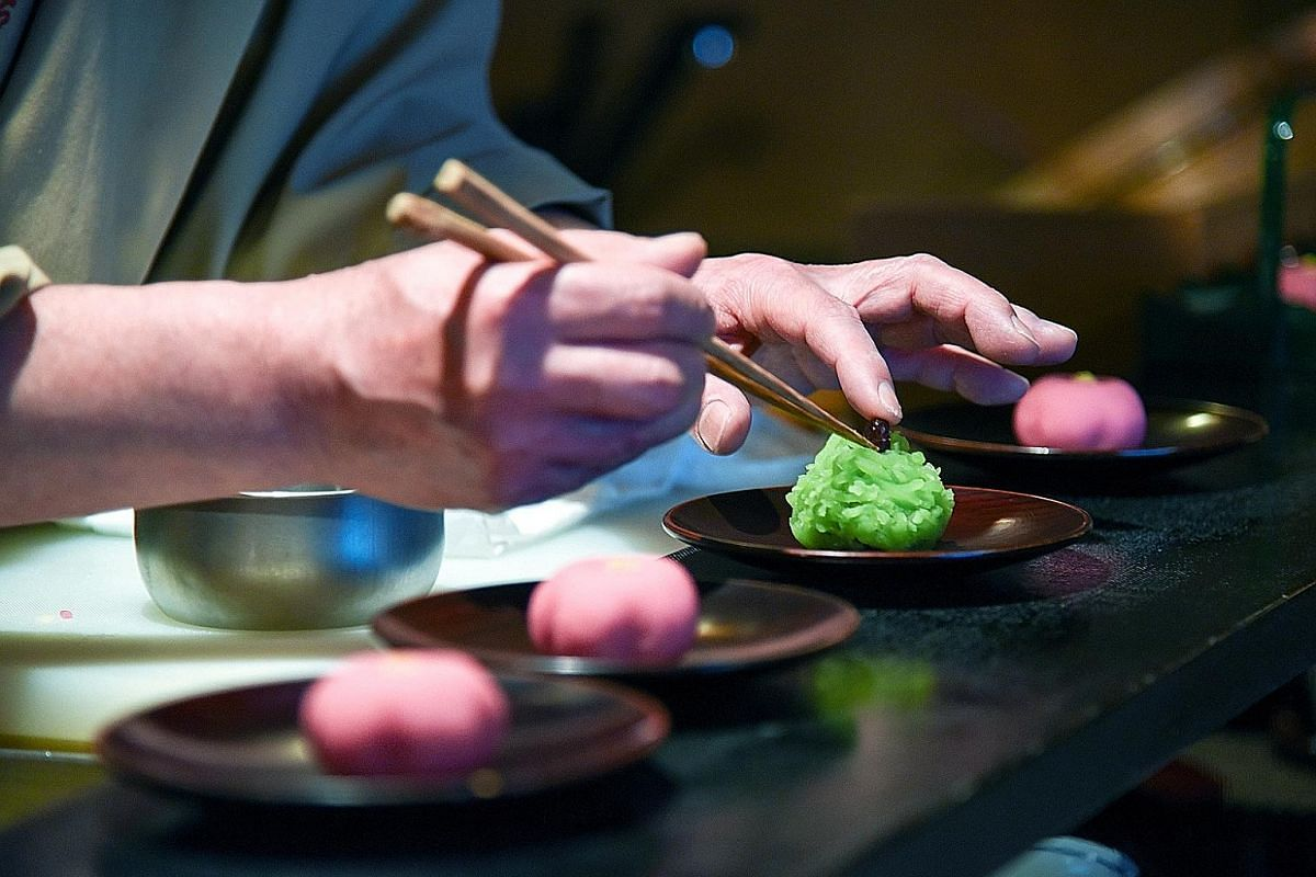 A confectioner at Tsuruya Yoshinobu, a shop in Kyoto known for its tea ceremony sweets, putting the finishing touches to a cake meant to suggest pine trees.