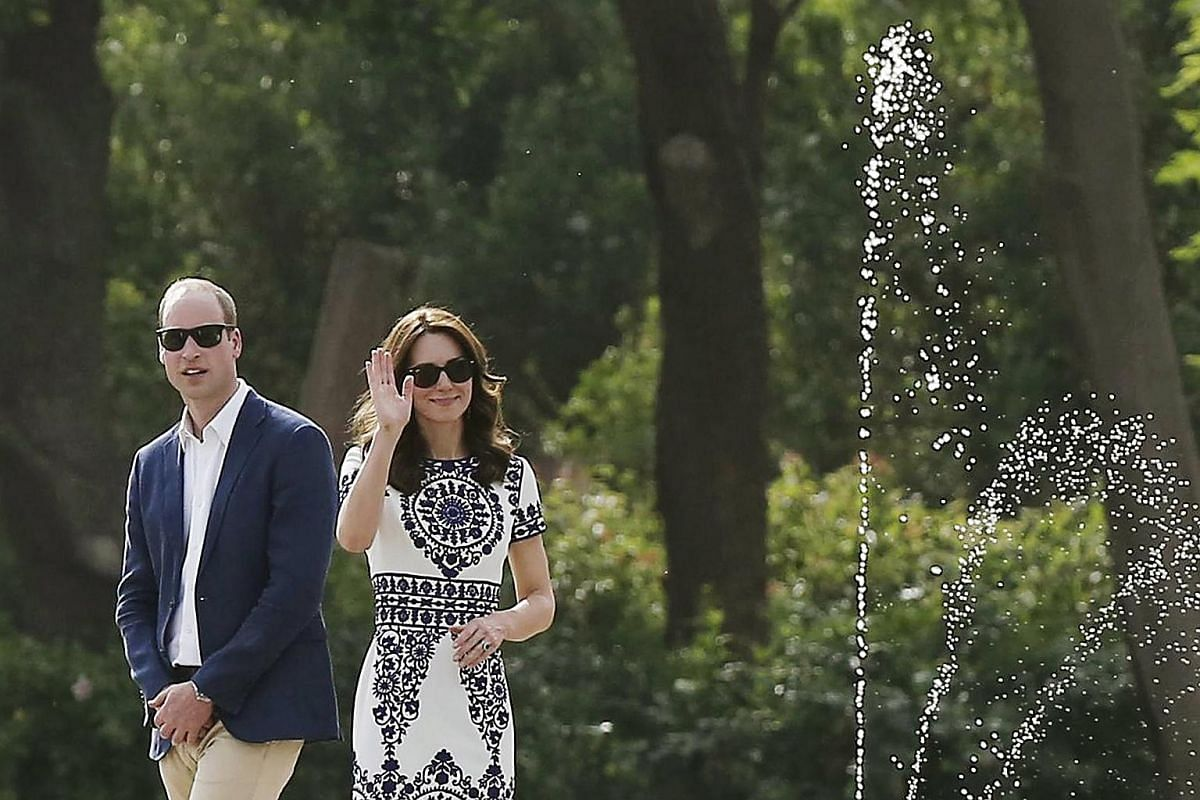 Catherine, the Duchess of Cambridge, waves as Britain's Prince William looks on during their visit to the Taj Mahal in Agra, India, on April 16, 2016.