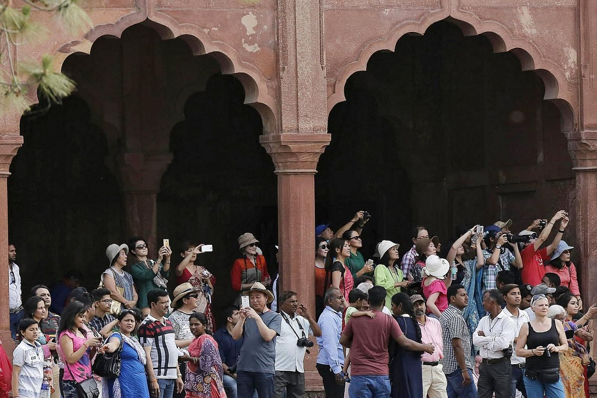 Visitors take pictures of Britain's Duke and Duchess of Cambridge, as they visit the Taj Mahal in Agra, India, on April 16, 2016.