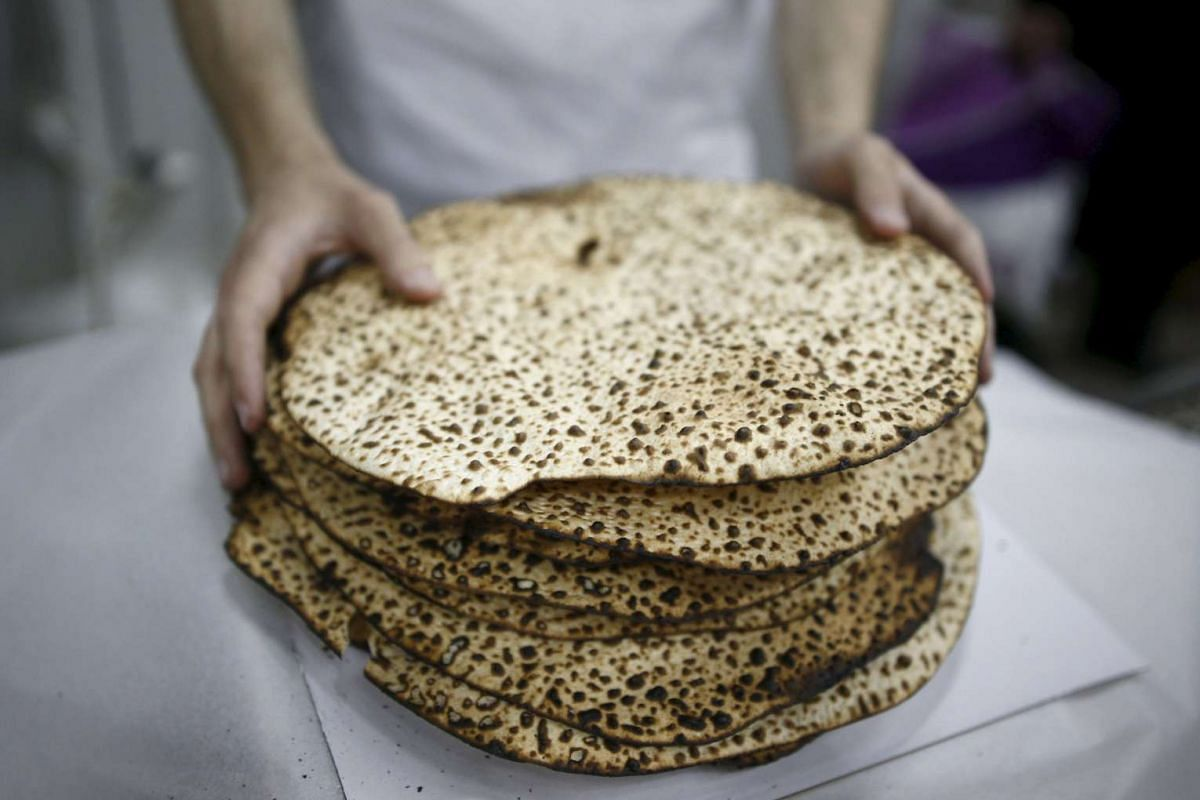 An ultra-Orthodox Jewish wraps fresh matza, traditional unleavened bread eaten during the Jewish holiday of Passover, in the southern city of Ashdod, on April 17, 2016.