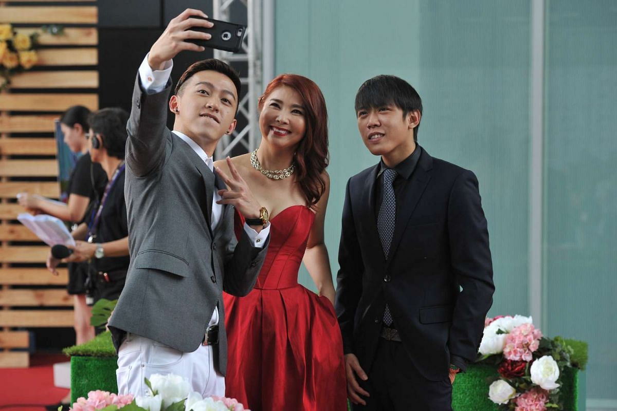 Ah Boys to Men actors Tosh Zhang (left) and Wang Weiliang (right) take a wefie with Chen Xiuhuan on the red carpet of the Star Awards 2016.