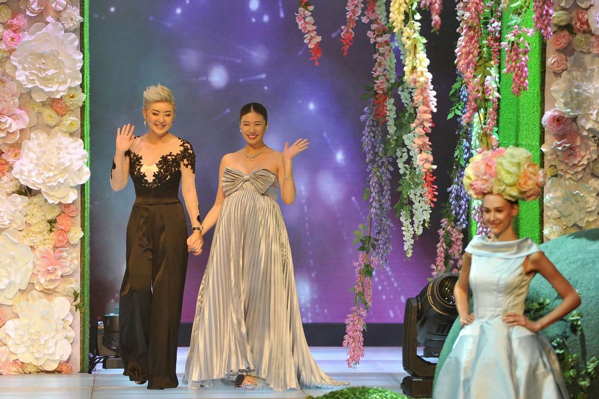 Quan Yi Fong (left) and a pregnant Kate Pang walk on stage to present an award during the Mediacorp Star Awards 2016.