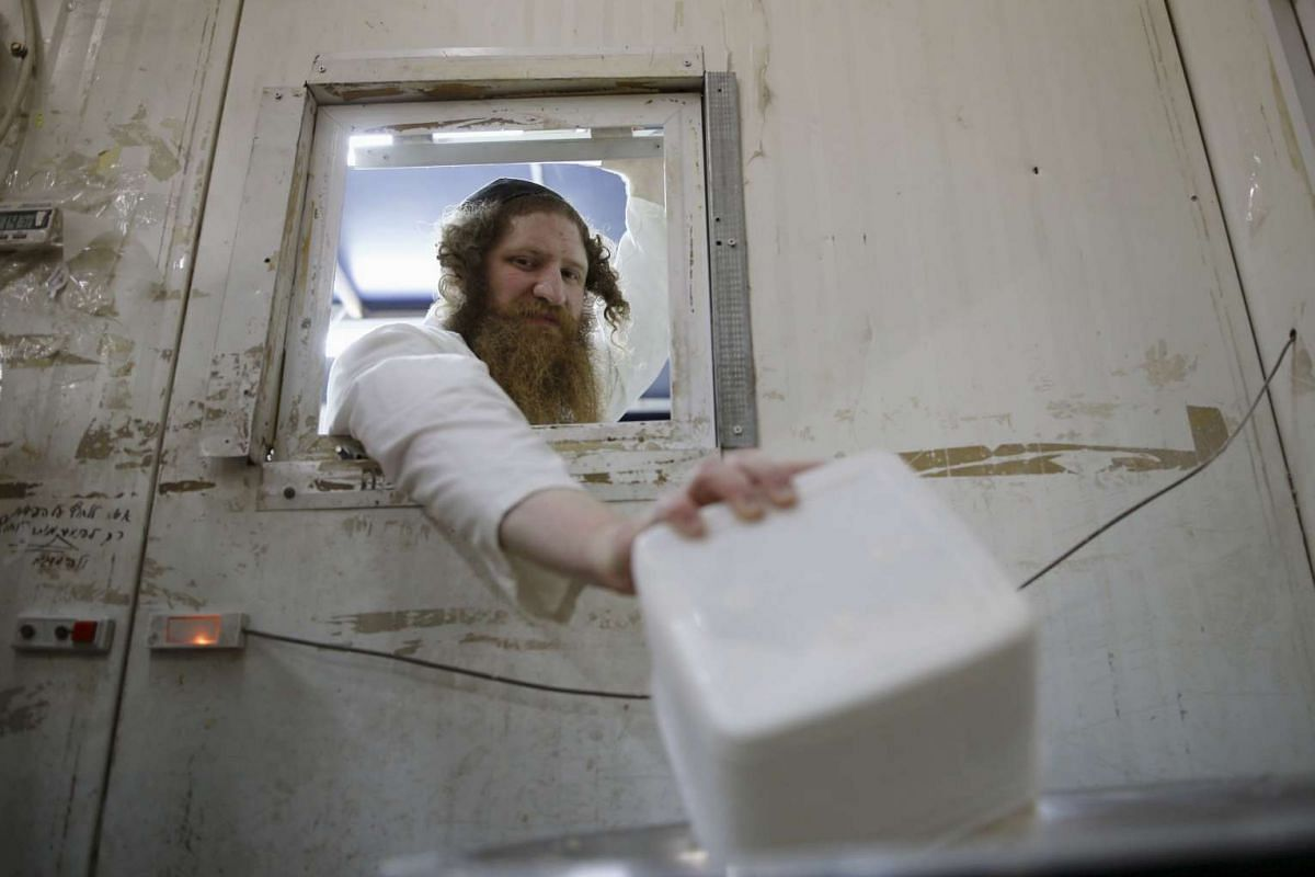 An ultra-Orthodox Jewish man pours flour into a bowl as he prepares matza in Ashdod, on April 17, 2016.