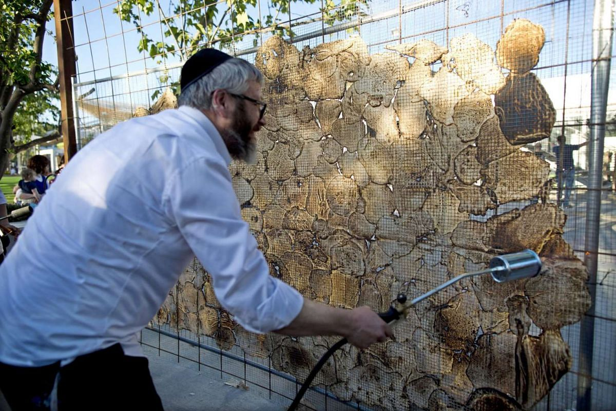 Ultra-Orthodox Jewish man uses a gas torch to cook a large matzah in Jerusalem, Israel, on April 17, 2016.