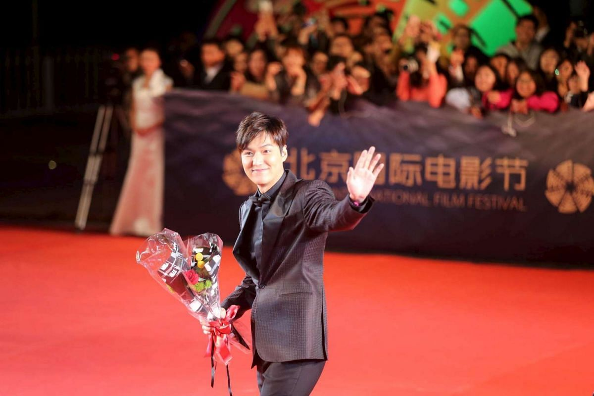 South Korean actor Lee Min Ho waves to fans on the red carpet.