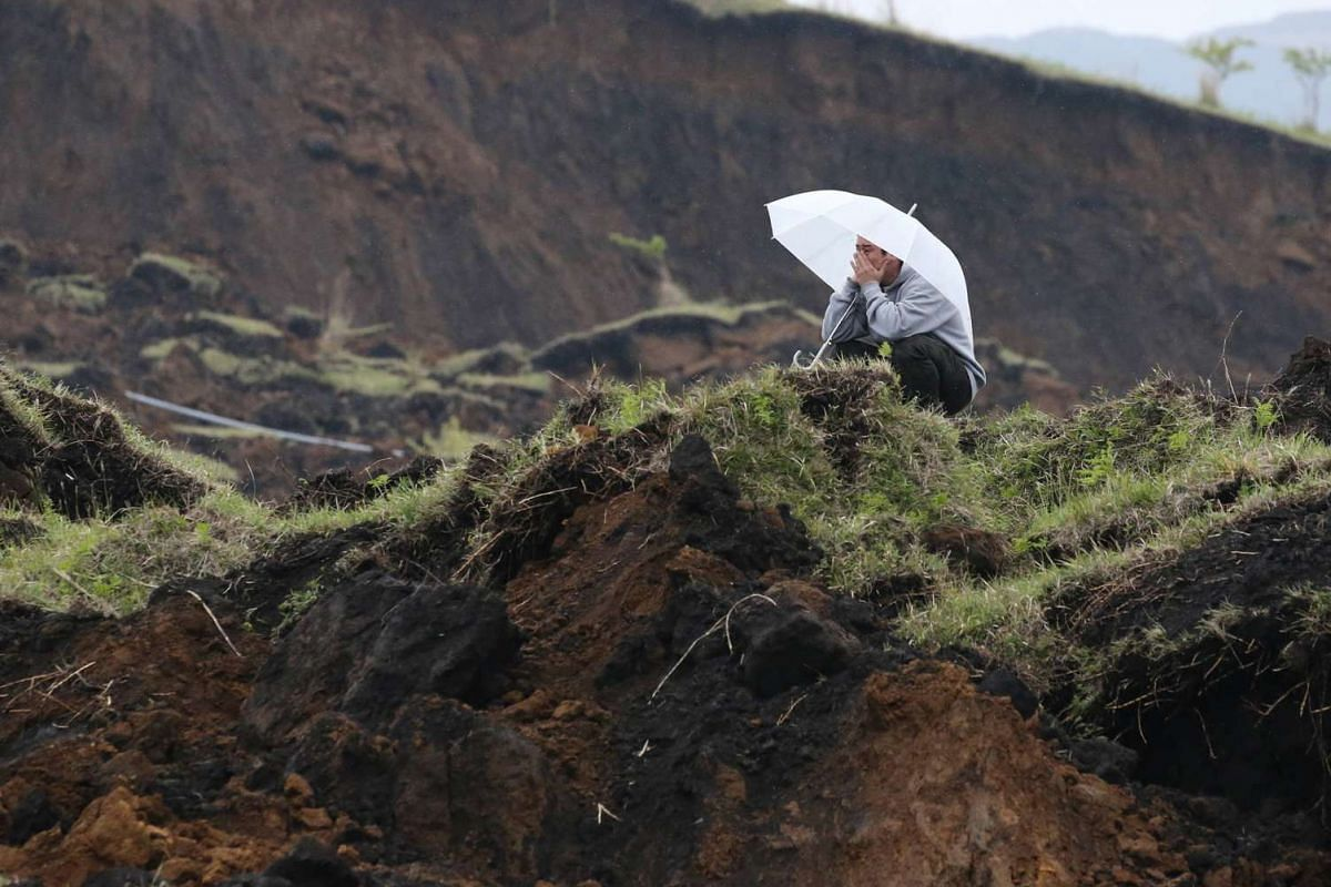 A man covering his face while looking over an area which collapsed due to the strong earthquakes in the village of Minami-Aso in Kumamoto prefecture on April 18, 2016.