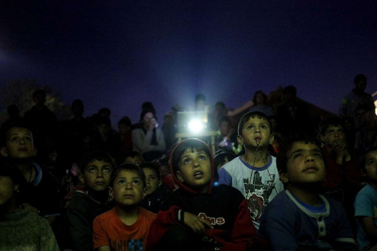 Children watch a cartoon movie, screened at a makeshift camp for migrants and refugees at the Greek-Macedonian border near the village of Idomeni, Greece, on April 17, 2016.