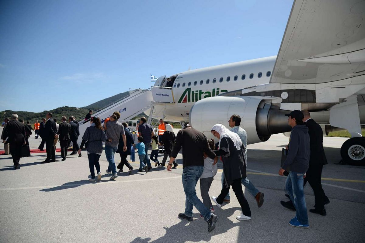 A group of Syrian refugees arrive for their flight with Pope Francis at Mytilene Airport on April 16, 2016.