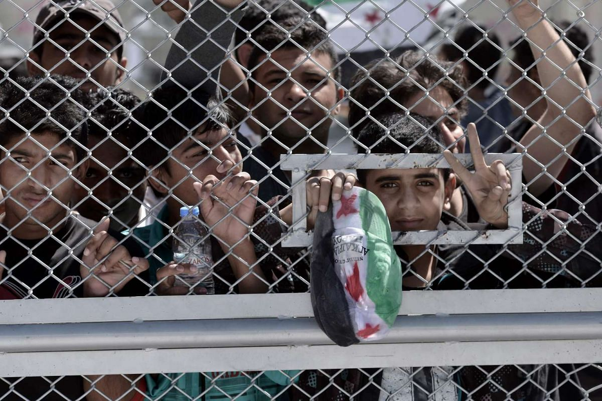 A young migrant flashes the victory sign while holding a cap with the national colours of the Syrian flag at the Moria detention centre during a visit by Pope Francis to Mytilene on April 16, 2016.