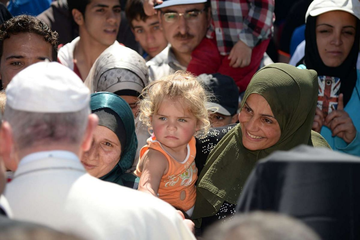 Pope Francis greets migrants and refugees at the Moria refugee camp near the port of Mytilene on the Greek island of Lesbos on April 16, 2016.