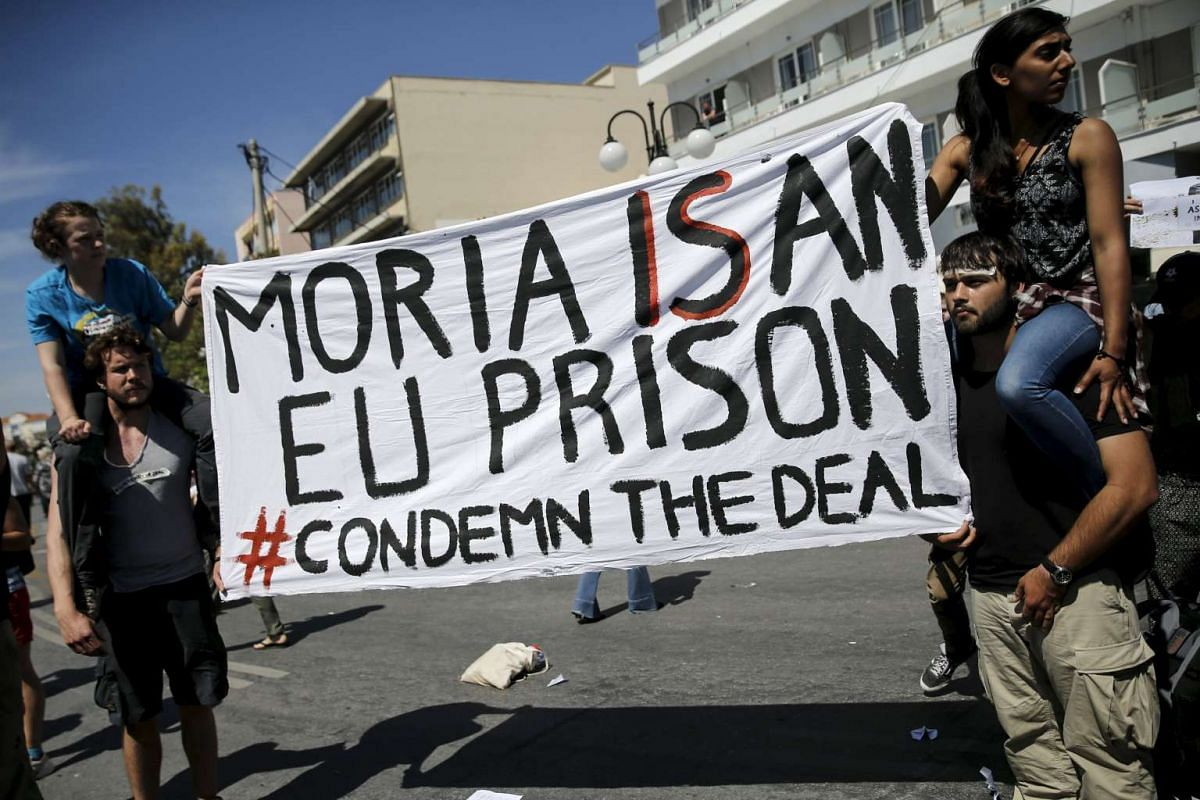 Activists protest against European Union immigration policies following the visit of Pope Francis to the port of Mytilene on the Greek Island of Lesbos on April 16, 2016.