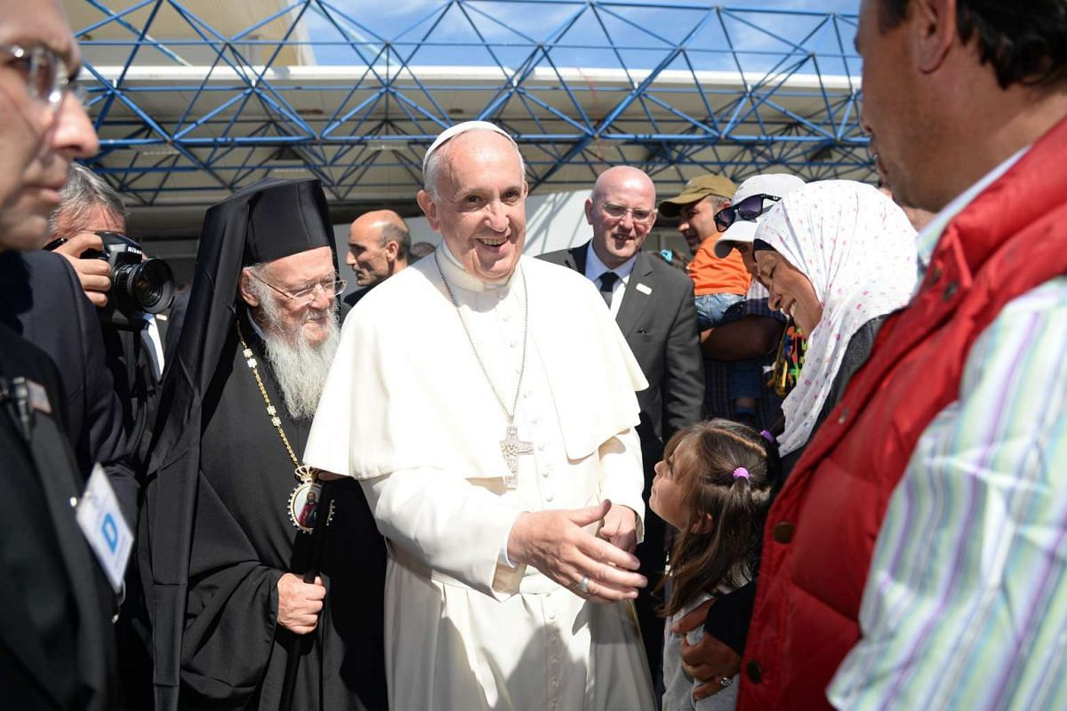 Pope Francis (centre) greets a group of Syrian refugees who will fly back to the Vatican with him on April 16, 2016.