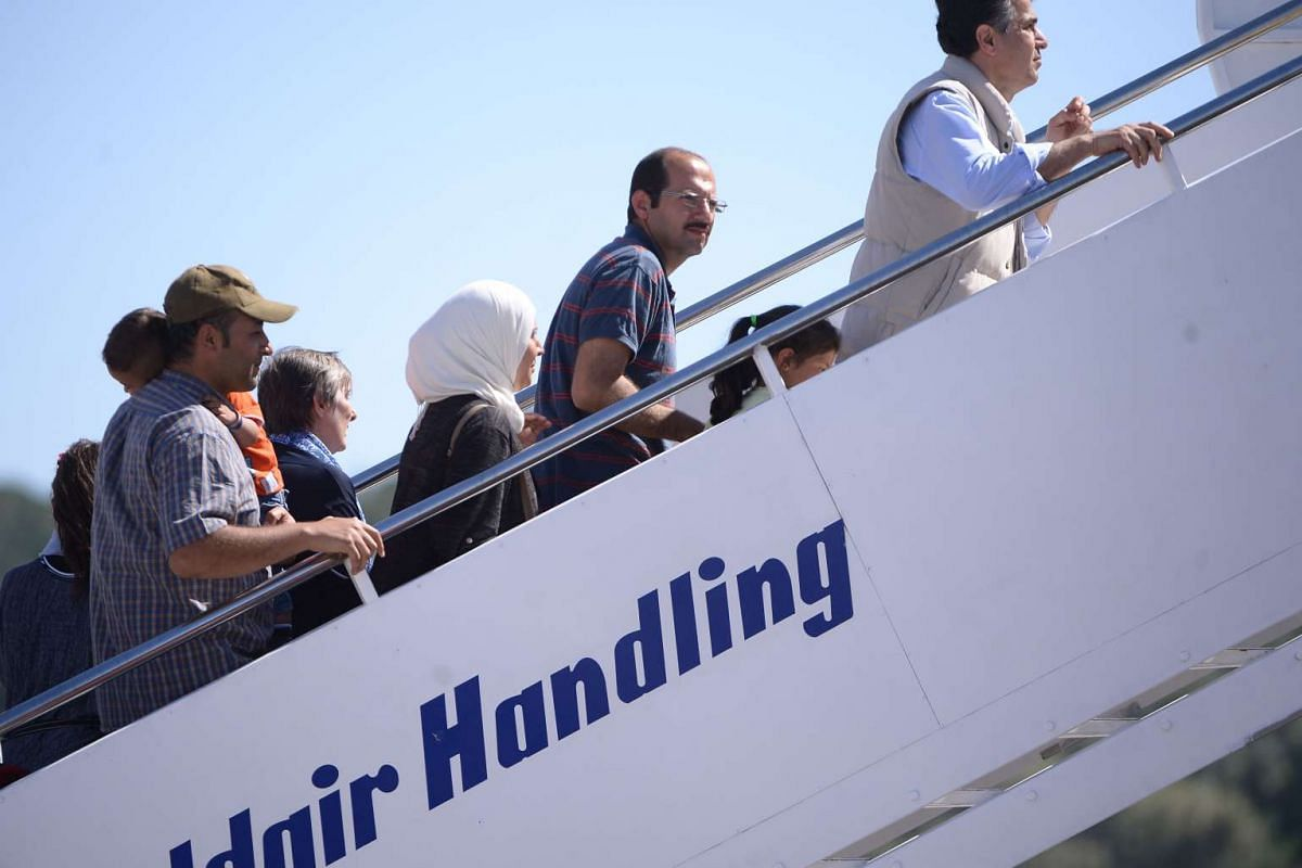A group of Syrian refugees board a plane with Pope Francis at Mytilene Airport on April 16, 2016.
