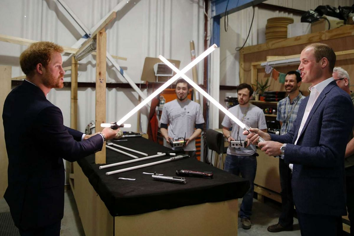 Britain's Prince William (right) has a lightsaber duel with his brother Prince Harry during a visit to the Star Wars film set at Pinewood Studios, London, on April 19, 2016.