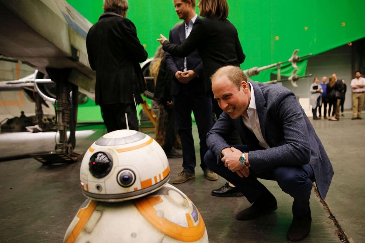Britain's Prince William  smiles at BB-8 during a tour of the Star Wars sets at Pinewood studios, London, on April 19, 2016.