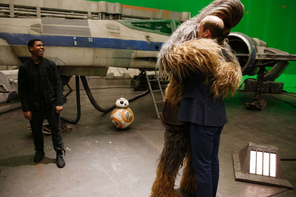 Britain's Prince William (right) is hugged by Chewbacca as actor John Boyega smiles during a tour of the Star Wars sets at Pinewood studios, London, on April 19, 2016.