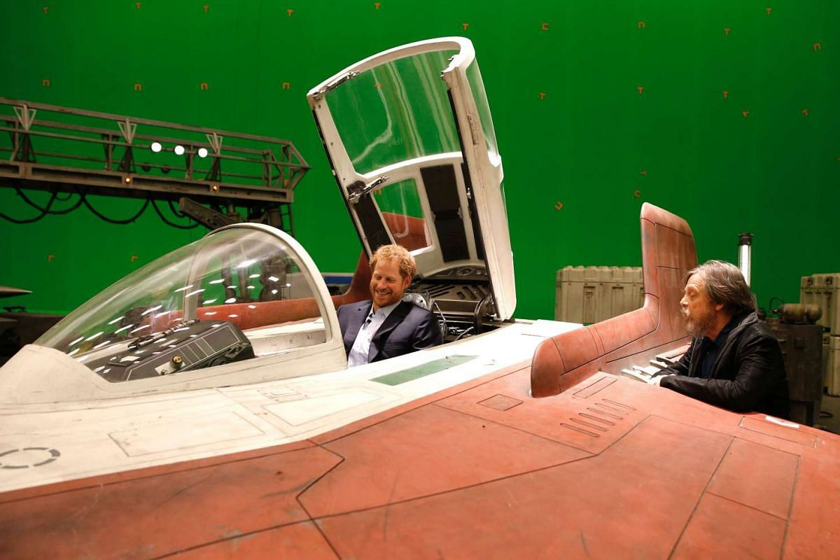 Britain's Prince Harry sits in an A-wing fighter as he talks with actor Mark Hamill during a tour of the Star Wars sets at Pinewood studios, London, on April 19, 2016.