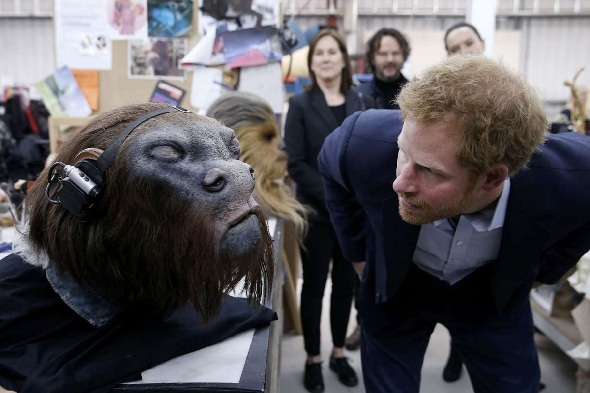 Britain's Prince Harry takes a closer look at a robotic mask during a tour of the Star Wars sets at Pinewood studios, London, on April 19, 2016.