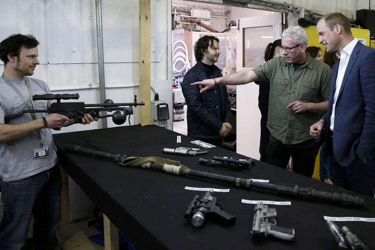 Britain's Prince William is shown props including Chewbacca's crossbow (left) during a tour of the Star Wars sets at Pinewood studios, London, on April 19, 2016.