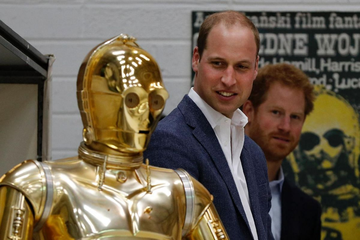Britain Prince William (centre) and Britain's Prince Harry look at C3P0 as they visit the creature and droid department at Pinewood studios, London, on April 19, 2016.