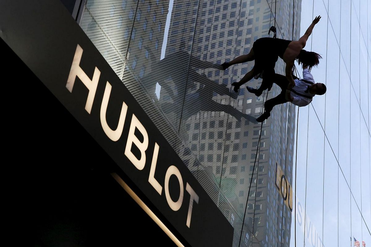 Dancers rappelling down the side of a building as part of a performance during a ribbon cutting ceremony to celebrate the opening of the flagship Hublot store on Fifth Avenue in Manhattan, New York, on April 19, 2016.