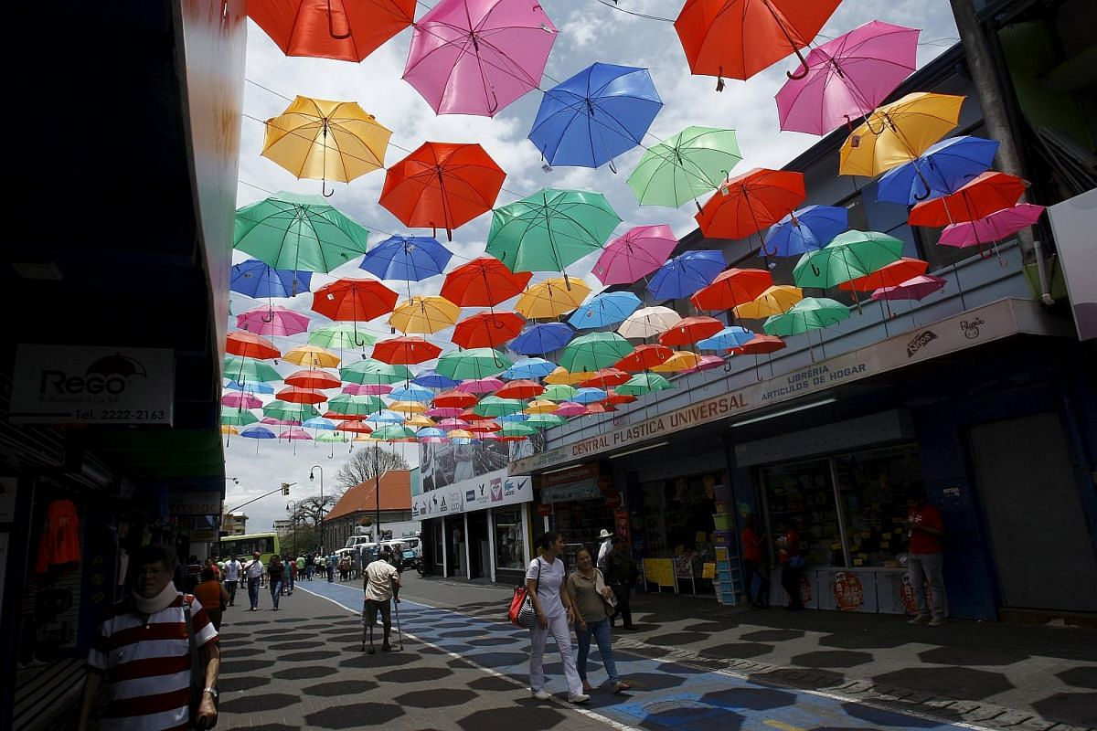 People walking under a collection of umbrellas placed on a boulevard to promote their sale as winter approaches in San Jose, Costa Rica on April 19, 2016.