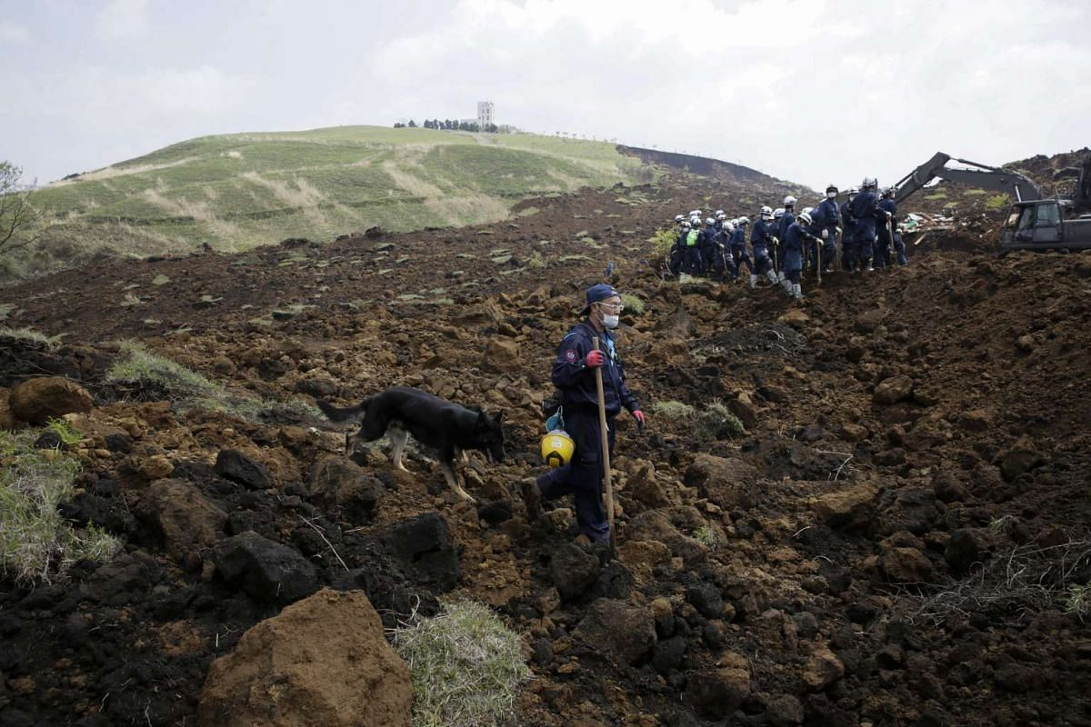 Rescue workers with a sniffing dog searching for missing people at the site of a massive landslide triggered by a 7.3 magnitude earthquake on 16 April, where eight people are reported still missing, in Minamiaso, Kumamoto Prefecture, southwestern Jap