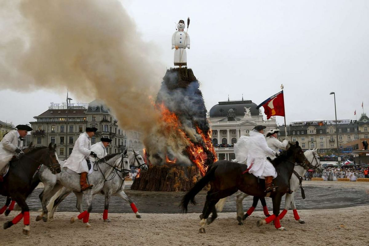 Mounted guildsmen gallop around the Boeoegg, a snowman made of wadding and filled with firecrackers, as it burns atop a bonfire in the Sechselaeuten square in Zurich, Switzerland, on April 18, 2016.