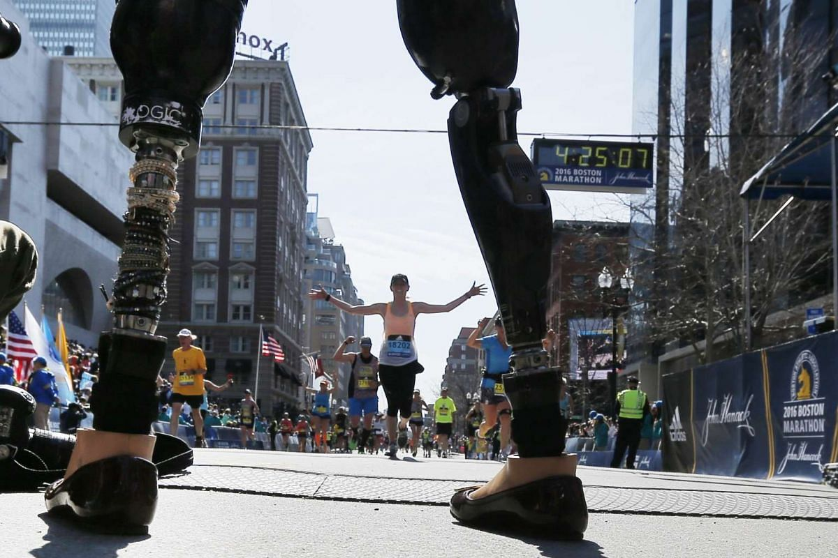 Celeste Corcoran, who lost both her legs in the Boston Marathon bombings, greeting runners at they finish the 120th running of the Boston Marathon in Boston, Massachusetts, on April 18, 2016.