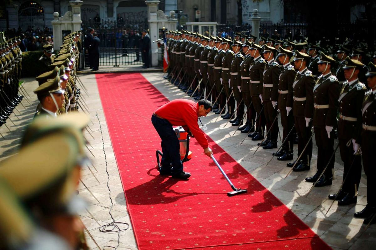 A man cleans a carpet before arrival of the casket containing the body of Chile's former president Patricio Aylwin at the Chilean Congress headquarters in Santiago, Chile on April 20, 2016.