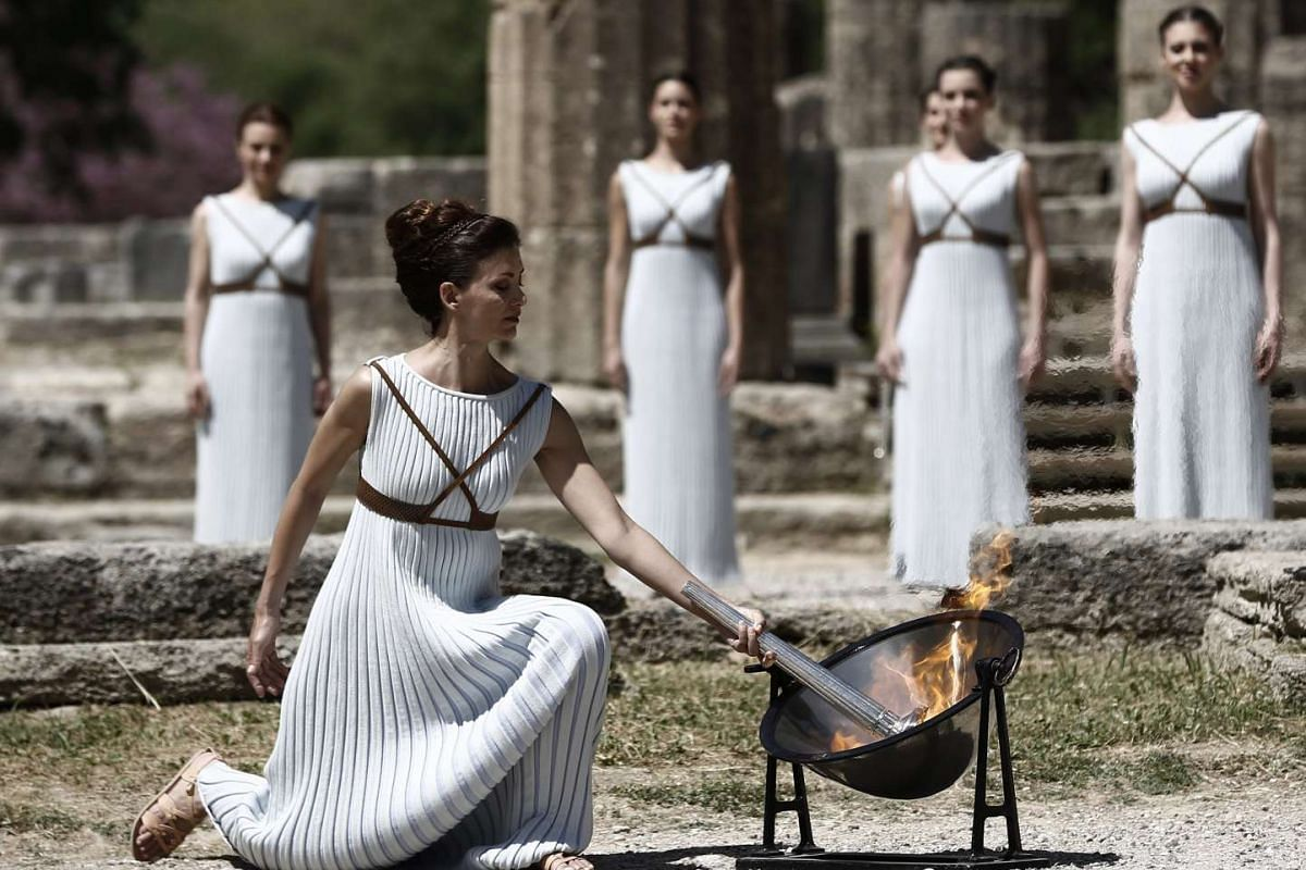 Greek actress Katerina Lechou, playing the role of High Priestess, lights a torch from sunrays reflected on a parabolic mirror during the rehearsal of the Lighting Ceremony of the Rio 2016 Olympic Games at the site of ancient Olympia in Greece on Apr