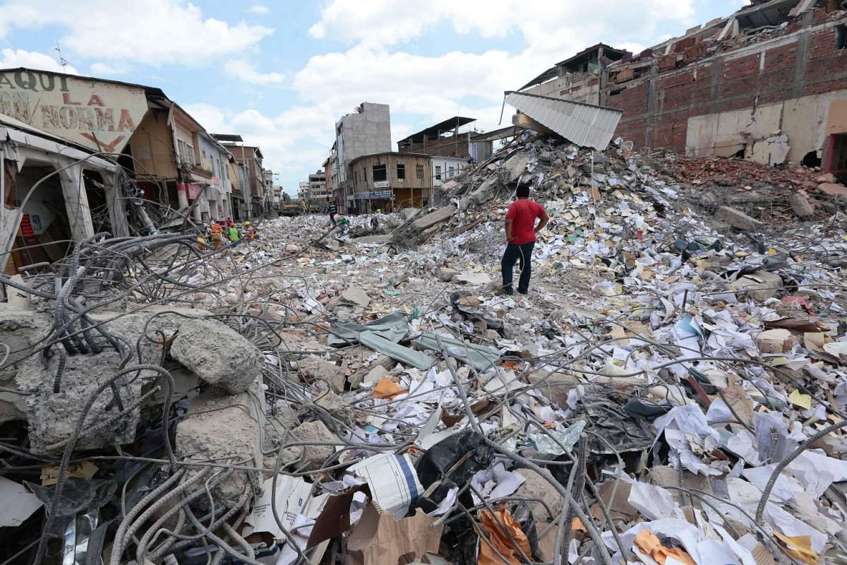 A man stares at the rubble in Portoviejo on April 20, 2016 after the devastating earthquakes in Ecuador