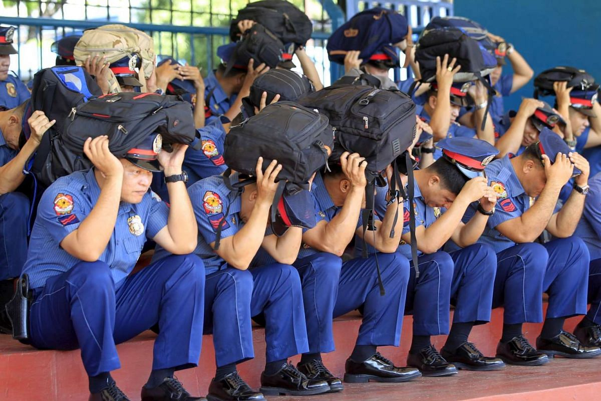 Members of the Philippine National Police use their personal handbangs to cover their heads to avoid injuries during a simultaneous earthquake drill inside the police headquarters in Quezon city, metro Manila on April 21, 2016.