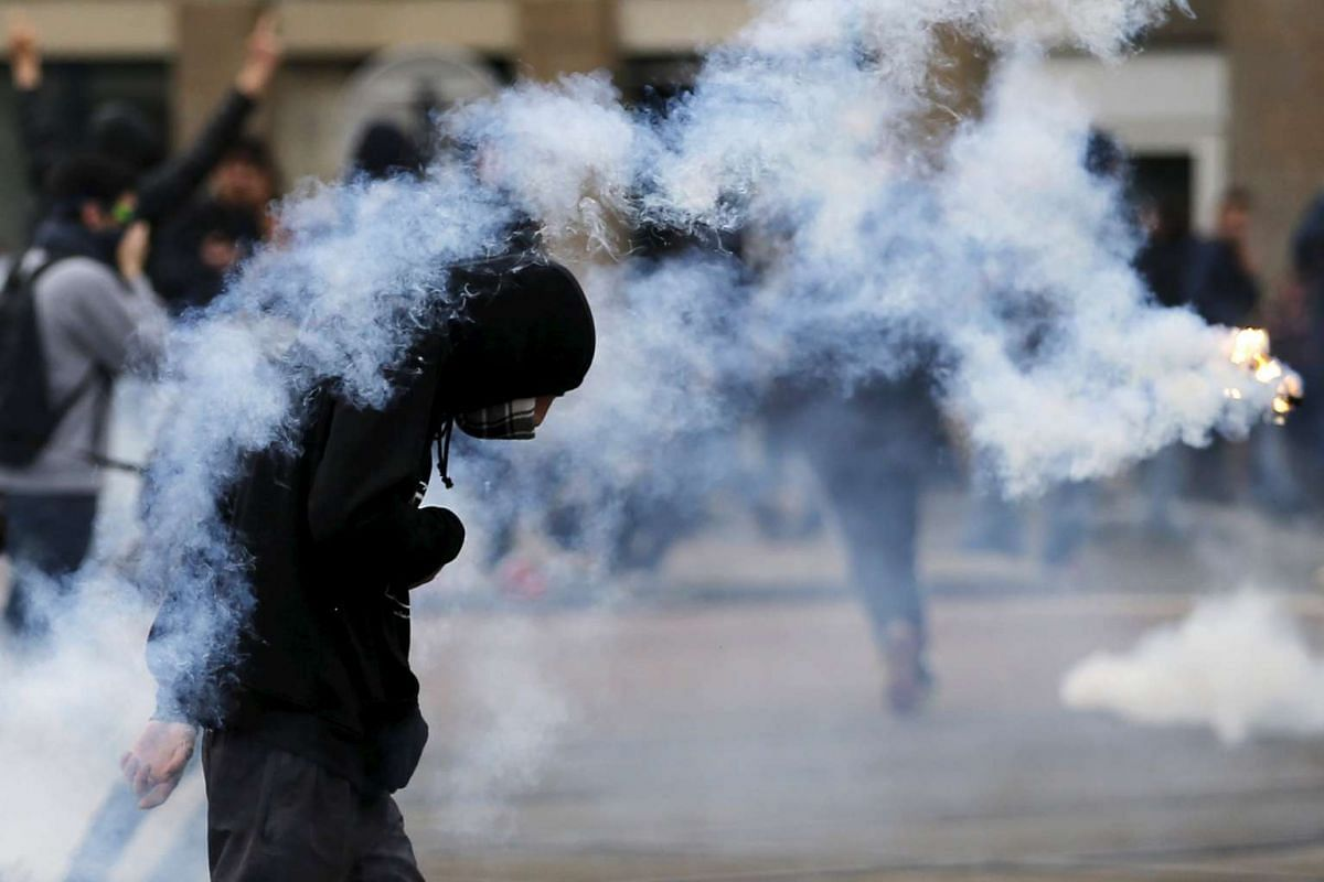 Youth takes cover from tear gas grenades during a demonstration against the French labour law proposal in Nantes, France on April 20, 2016.