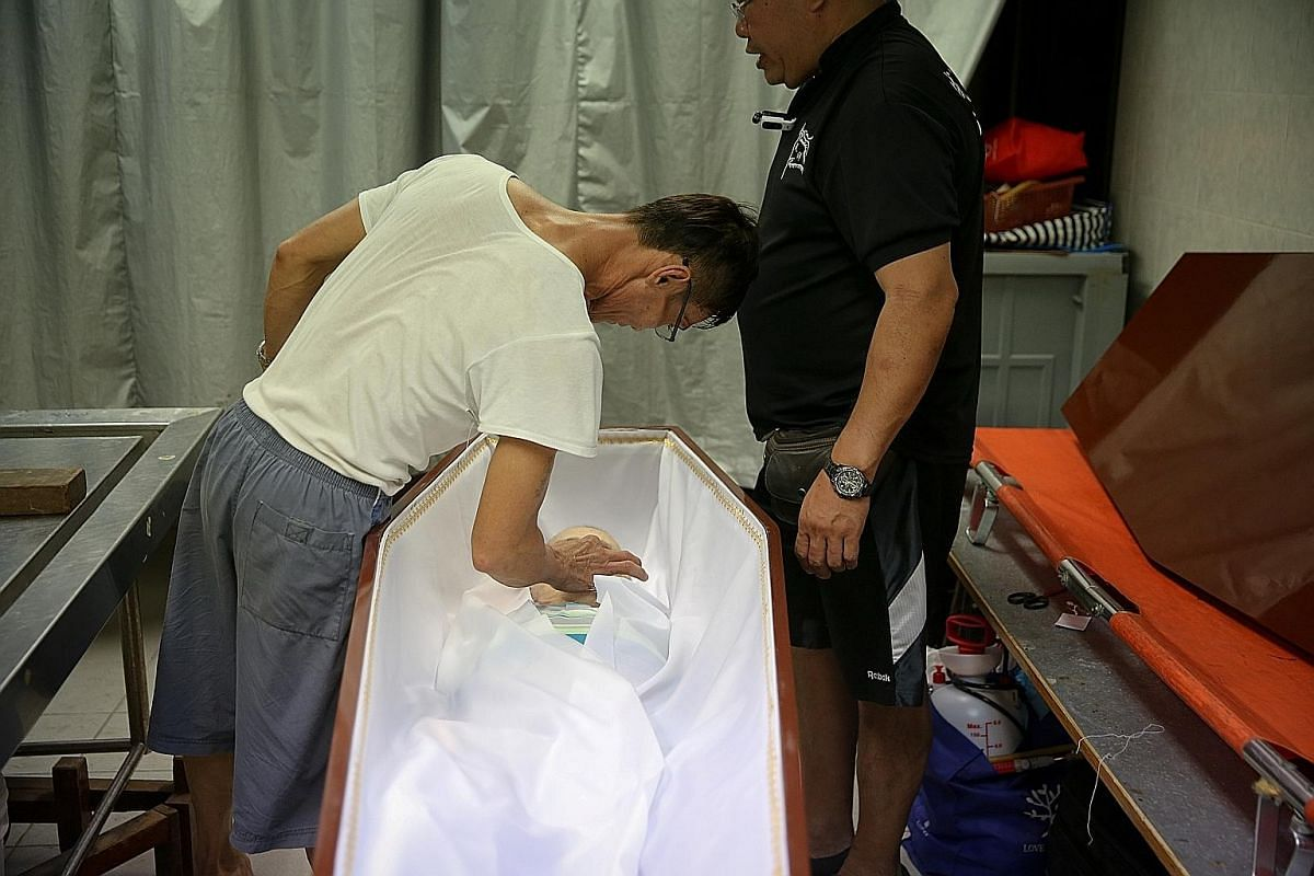 The body of Mr Hong, who had no known next of kin, being taken to the undertaker under Mr Yu's (in black) watchful eyes. Mr Yu shopping for clothes for Mr Hong. He bought a green-striped polo T-shirt, brown bermudas and black sandals. The undertaker