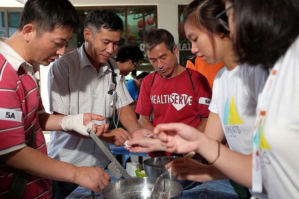 Students trying their hand at soap-making at the Community Engagement Festival of NUS' College of Alice & Peter Tan - after working together in groups to clean soap slivers collected from hotels, they reconstitute them using a simple hand-operated ma