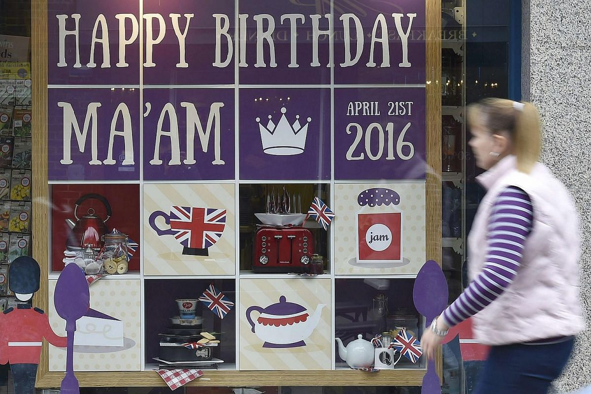 A woman walks past a window display themed for the forthcoming birthday of Britain's Queen Elizabeth.