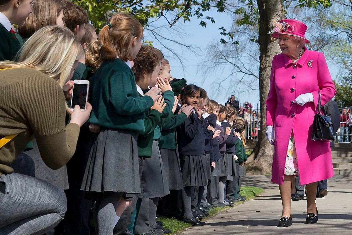 Britain's Queen Elizabeth II smiles as she is greeted by school children as she arrives to open a bandstand at Alexandra Gardens in Windsor, on April 20, 2016, the day before her 90th birthday.