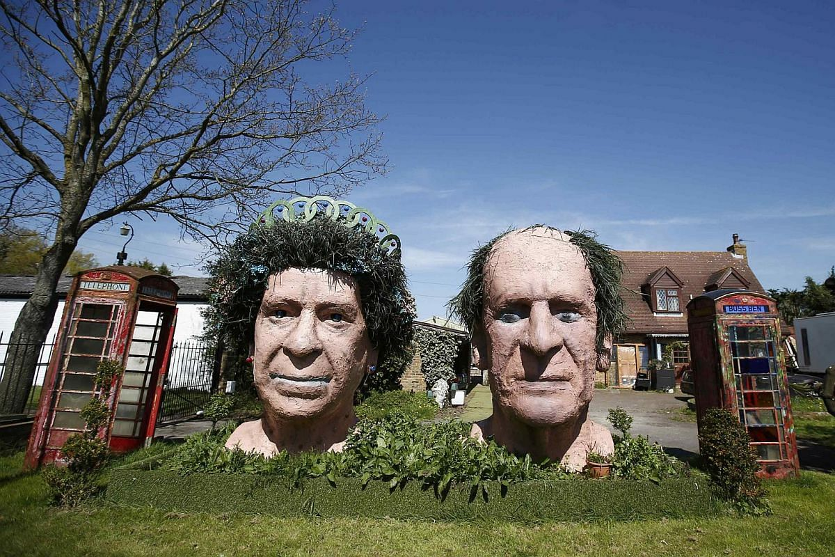 Two giant terracotta busts of Britain's Queen Elizabeth and Prince Philip on display in the garden of Fifield House Farm.