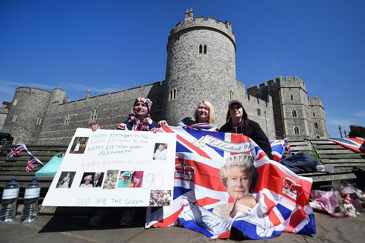 Royal well-wishers hold a placard and national flag with pictures of Britain's Queen Elizabeth II outside Windsor Castle one day ahead of the Queen's birthday.