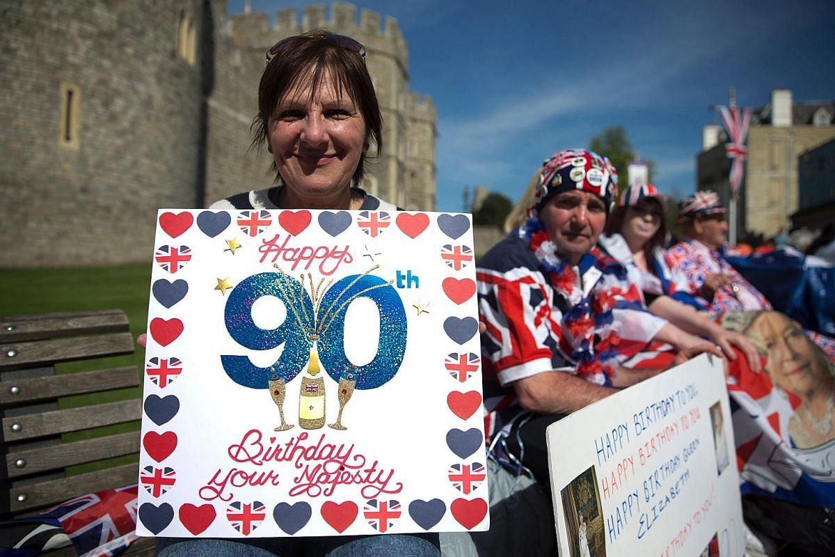 Royal well-wishers hold placards wishing Britain's Queen Elizabeth II a happy 90th birthday.