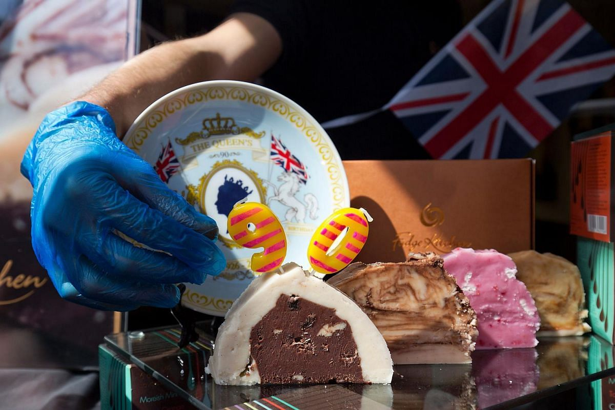 A shop assistant adjusts candles in a cake to celebrate the birthday of Britain's Queen Elizabeth II at a gift shop in Windsor.