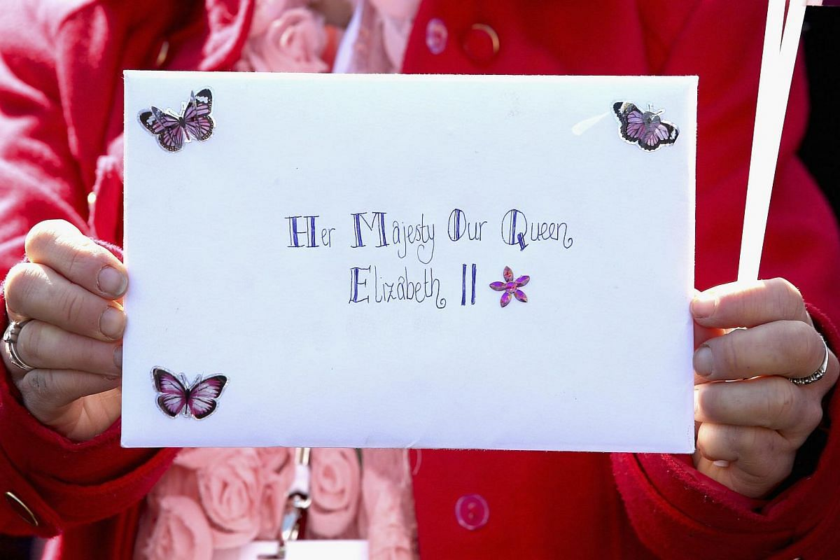 A member of the public holds up a card for Queen Elizabeth II as she visits the Queen Elizabeth II delivery office in Windsor.