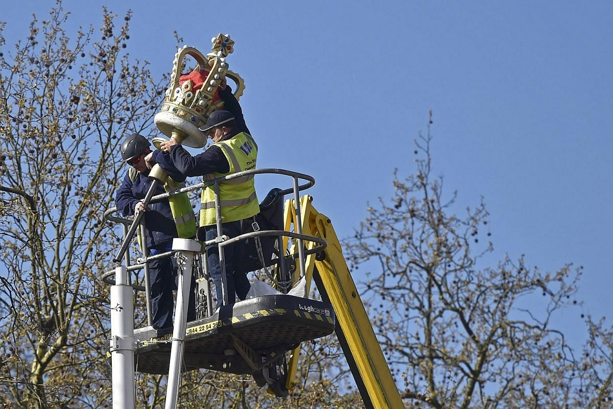Workers place a mould representation of a crown on a flagpole along a Mall in London.
