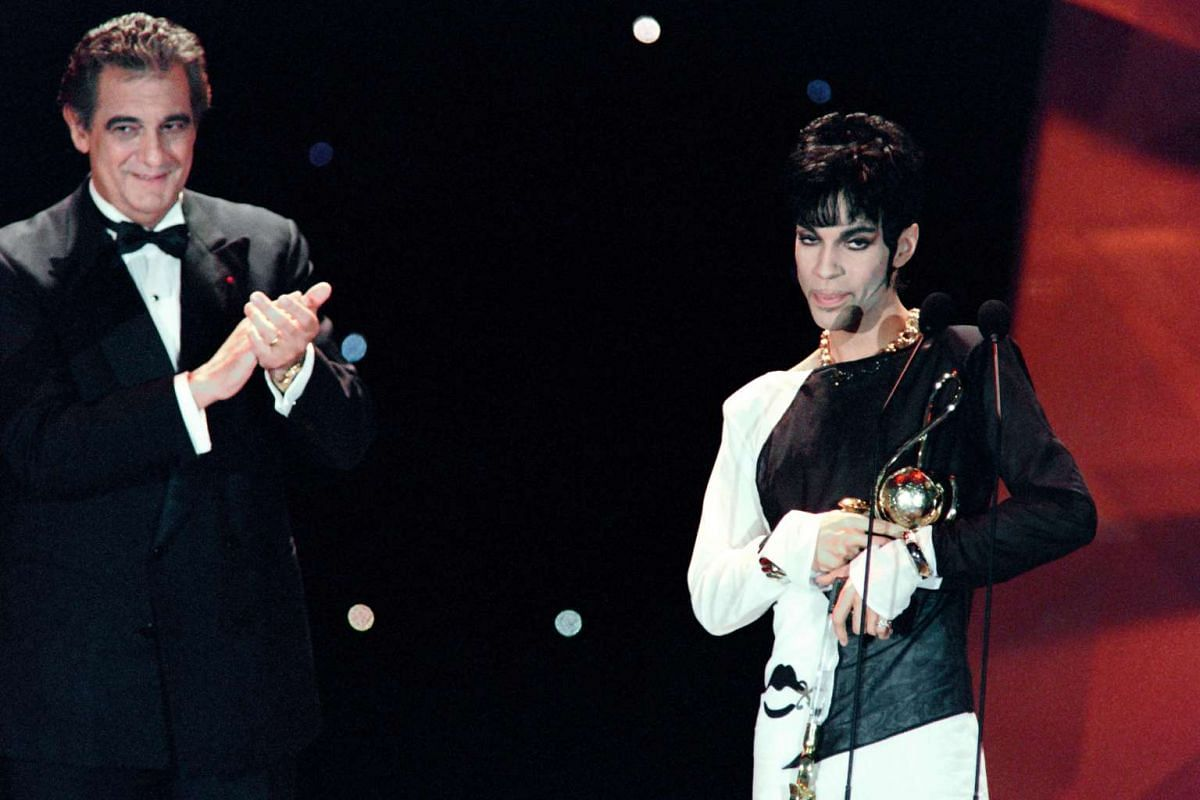 Prince (right) receiving from Italian tenor Placido Domingo the Outstanding Contribution to the Pop Industry award during the World Music Awards ceremony in Monaco, on May 4, 1994.