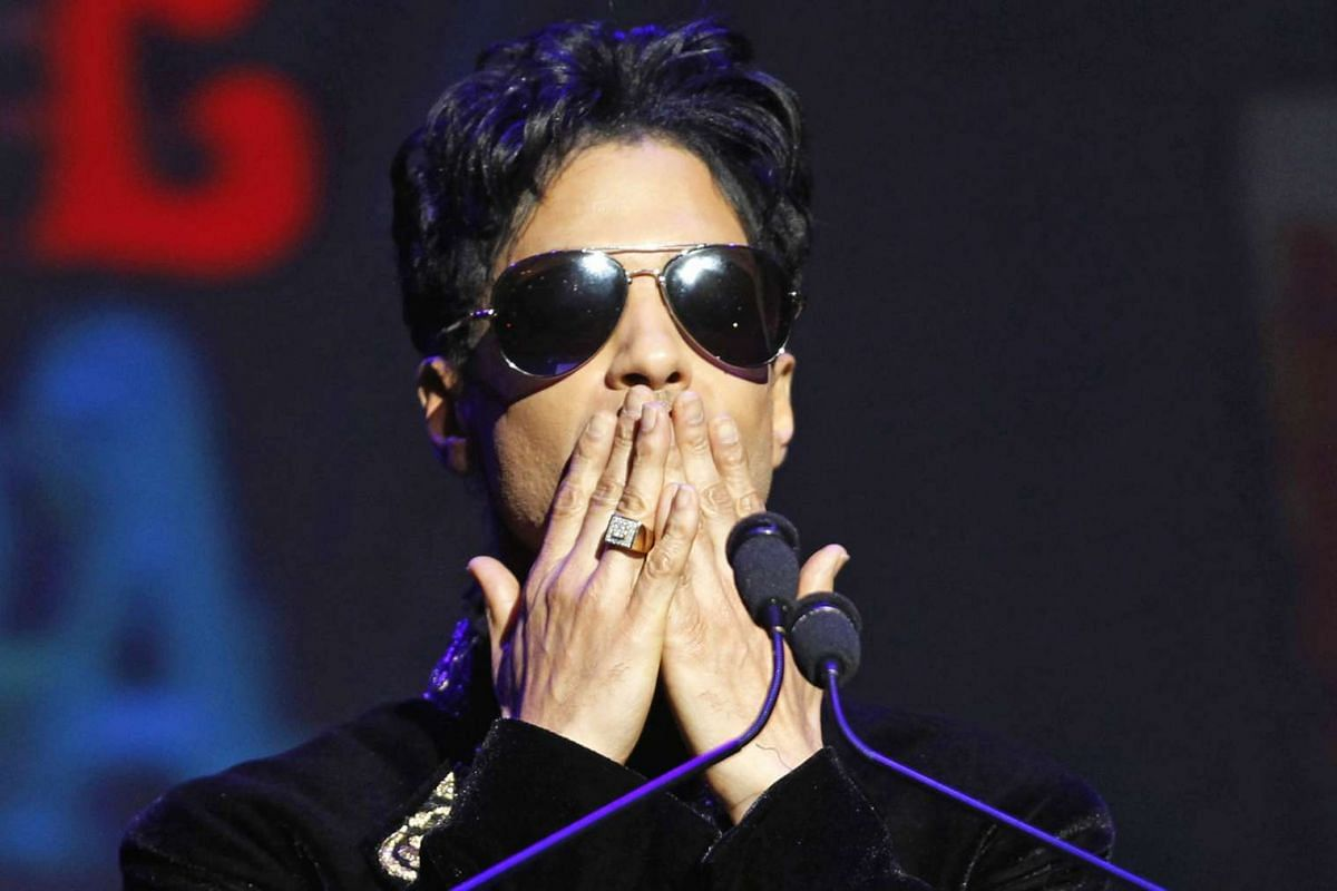 Prince gesturing as he announces upcoming live dates at the Apollo Theater in New York, on Oct 14, 2010.