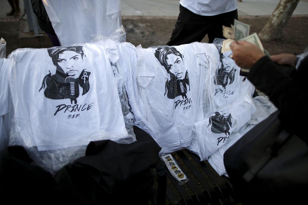 People buying t-shirts at a vigil to celebrate the life and music of deceased musician Prince in Los Angeles, California, on April 21, 2016.